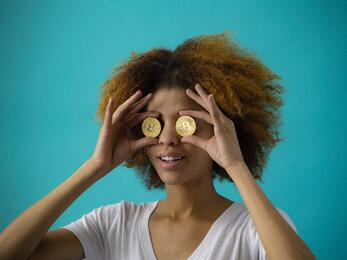 "Young woman holding ""blockchain"" coins in front of her eyes"